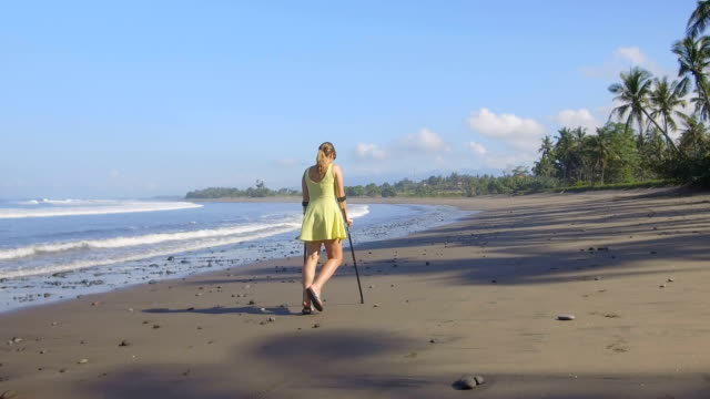 CLOSE UP Girl with crutches walking down the sandy beach on tropical island Bali CLOSE UP: Strong independent woman walking with crutches along the sandy beach on summer vacation at tropical island Bali. Girl with leg injury strolling along shore with palm trees enjoying holidays crutch stock videos & royalty-free footage