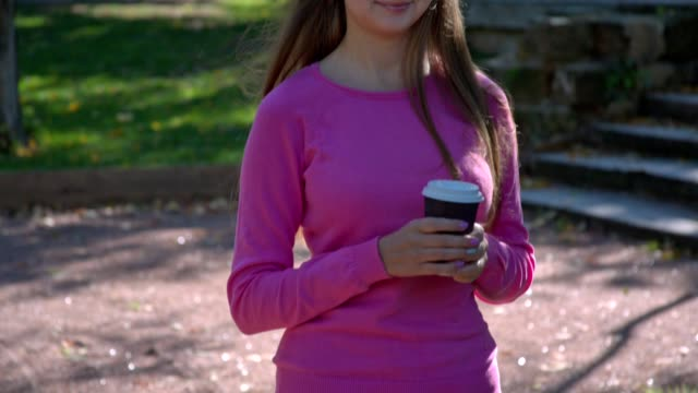 Girl with cup of coffee in park video