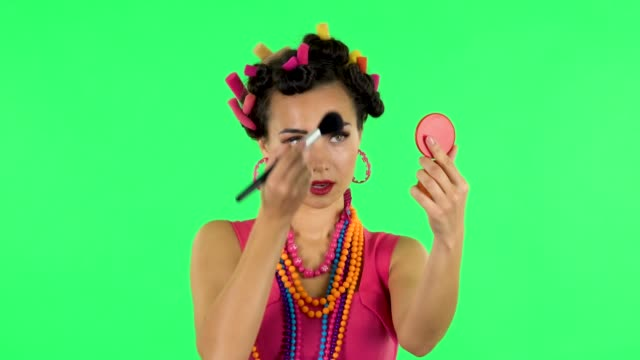 Girl with curlers on her head in a pink dress looking in red mirror and powdered her nose with big brush. Green screen