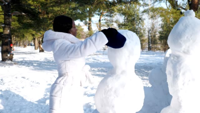 girl with dark skin builds snowman having fun in forest