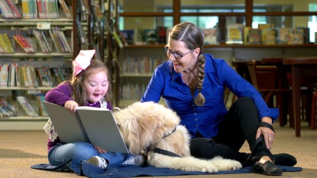 図書館でダウン症候群とセラピー犬を持つ女の子 - 支えられた点の映像素材/bロール