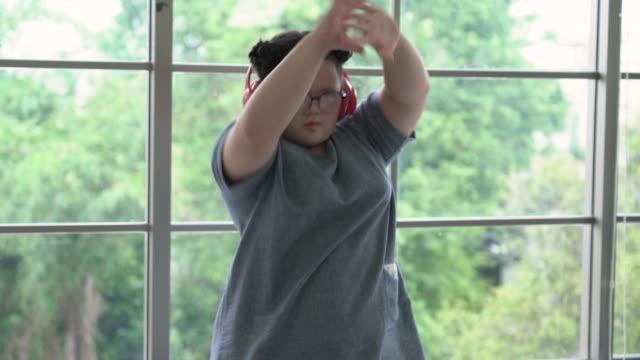flicka med downs syndrom dansar framför fönstret - endast en tonårsflicka bildbanksvideor och videomaterial från bakom kulisserna