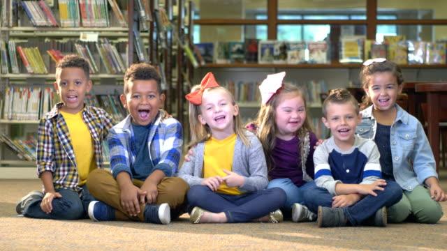 vidéos et rushes de fille avec le syndrome de down, amis dans la bibliothèque - élève