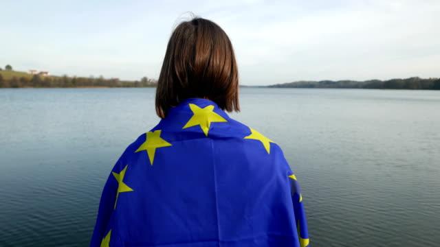 mädchen mit eu-flagge am see - europäische union stock-videos und b-roll-filmmaterial