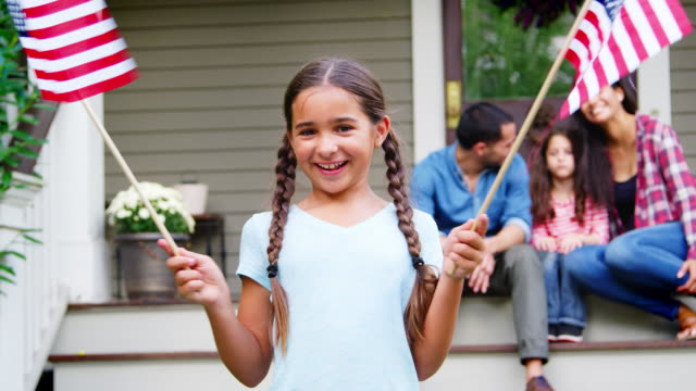 girl with family outside house holding american flags - giorno dell'indipendenza video stock e b–roll