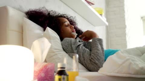 vidéos et rushes de fille avec de la fièvre à l'aide de thermomètre et une tablette dans le lit - froid