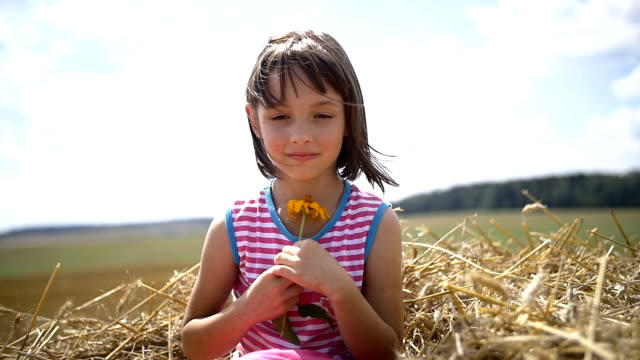 girl with flower looking at the camera and smiling, sitting on a mountain video