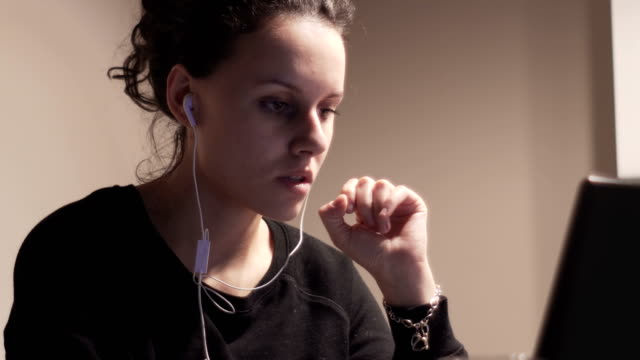 Girl with headphones listening to the music in a laptop