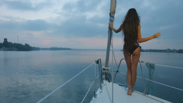 Girl with long hair enjoying a cruise on a sailing yacht. video