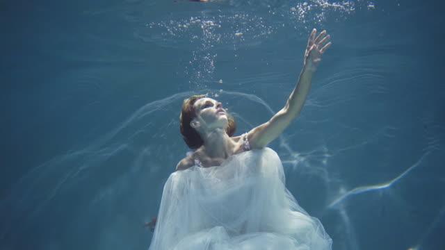 vidéos et rushes de fille avec les cheveux longs dans une robe blanche flottant sous l'eau - robe