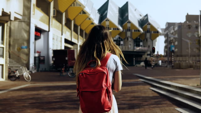 Girl with long hair walks by beautiful buildings. European local woman with red backpack. Cube House, Rotterdam. 4K