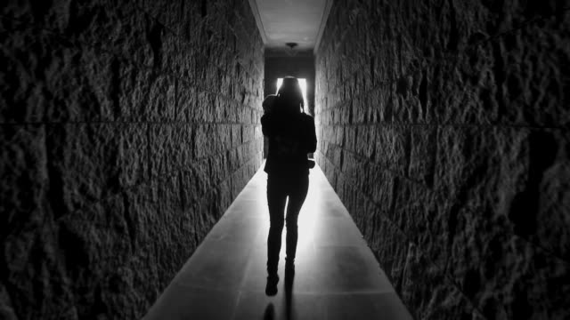 girl with long hair walks down a dark corridor tunnel with her back