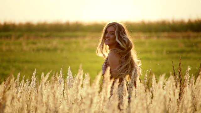 stockvideo's en b-roll-footage met een meisje met lang haar loopt door een gouden gebied in een romantische de zomerkleding onder tarweoren bij zonsondergang, langzame motie - blond curly hair