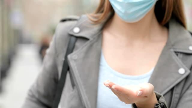 vídeos y material grabado en eventos de stock de chica con máscara limpiando manos con desinfectante de alcohol - hand sanitizer