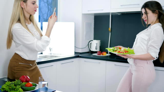 girl with mobile phone takes pictures of girlfriend holding dish with salad in hands at kitchen video