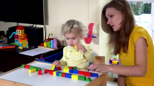 girl with mother playing colorful wooden bricks near small table at home video