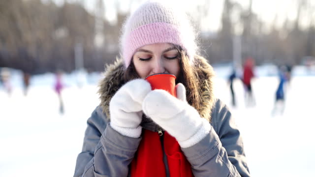 Girl with mug of hot drink on ice skating rink video