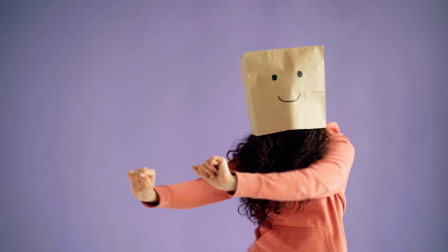 Girl with paper bag on head dancing showing thumbs-up showing like sign