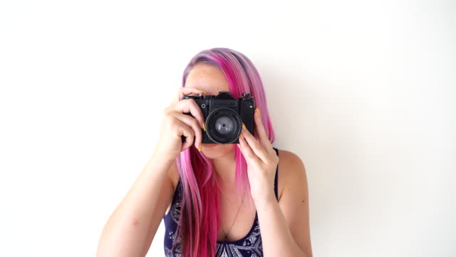 girl with pink hair makes photos on the vintage camera video
