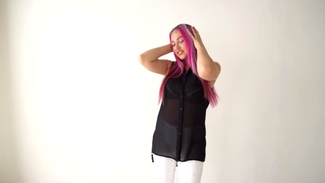 girl with pink hair posing in a white room video