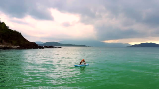 stockvideo's en b-roll-footage met meisje met paardenstaart stands in pose op paddleboard in de oceaan - paddle
