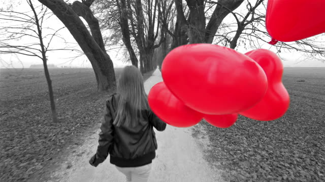 Girl with red heart shaped balloons running in a park video