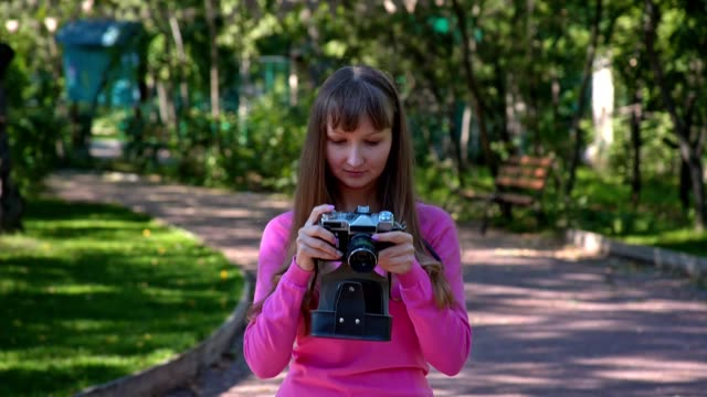 Girl with retro camera outdoors video