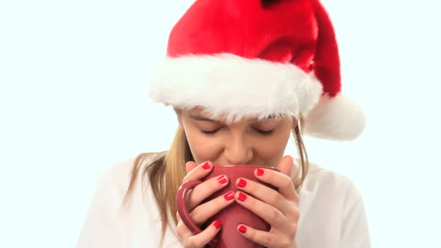 Girl with santa hat drinks from a coffee mug.