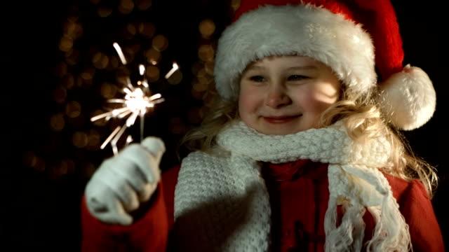 少女とサンタの帽子を、スパークラー - サンタの帽子点の映像素材/bロール