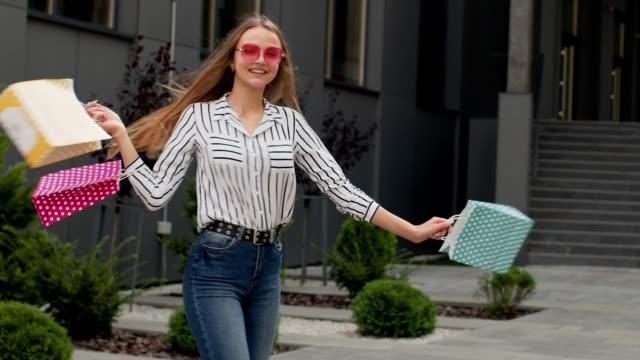 vídeos de stock, filmes e b-roll de garota com sacolas de compras, girando, dançando, olhando satisfeito com a compra, desfrutando de descontos de preço - arméria