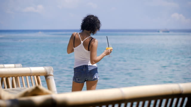 A girl with short hair, a T-shirt and denim shorts stands near the seaside on the island of Bali. She drinks a cocktail. Wonderful weather, the wind and the island promotes tranquility video