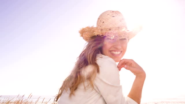 Girl with straw hat on the beach against blue sky video