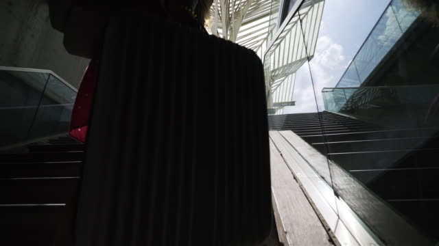 girl with suitcase climbing on stairs on platform - donna valigia solitudine video stock e b–roll