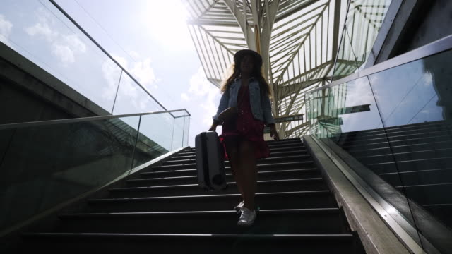 girl with suitcase walking downstairs on station - donna valigia solitudine video stock e b–roll