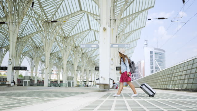 vídeos de stock e filmes b-roll de girl with suitcase walking on modern platform - people lisbon