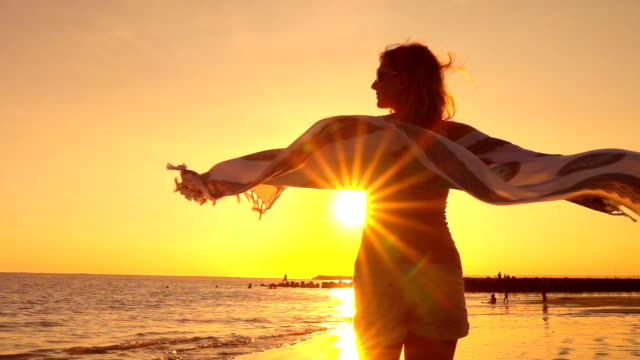 SLOW MOTION: Girl with sunglasses & fluttering scarf spinning on beach at sunset