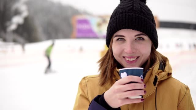 girl with takeaway coffee cup over ski resort background. beautiful young woman in knitted hat smiling. portrait - negozio sci video stock e b–roll