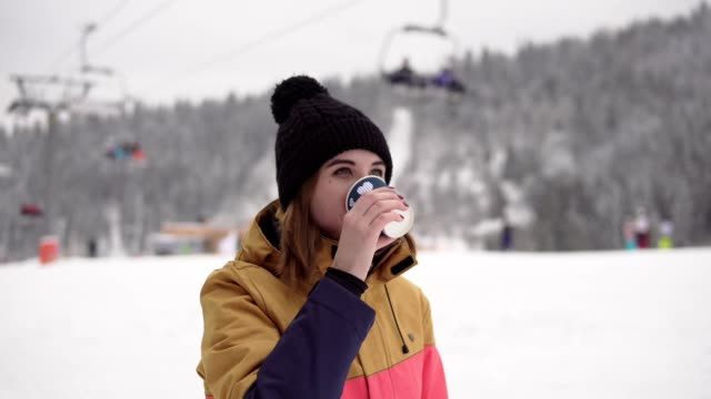 girl with takeaway coffee cup over ski resort background is drinking and waving someone. beautiful young woman in knitted hat smiling. portrait - negozio sci video stock e b–roll