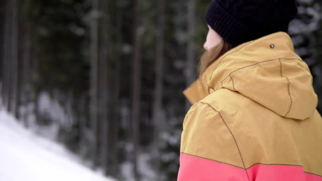 girl with takeaway coffee cup over ski resort background is walking on the snow. beautiful young woman in knitted hat. - negozio sci video stock e b–roll