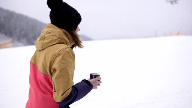 girl with takeaway coffee cup over ski resort background is walking on the snow. beautiful young woman in knitted hat. portrait - negozio sci video stock e b–roll