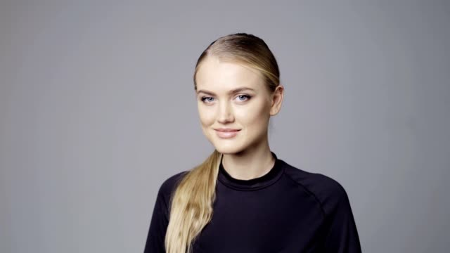 Girl with tied hair looking at camera smiling Portrait of young blond girl with tied hair looking at camera smiling over grey background ponytail stock videos & royalty-free footage