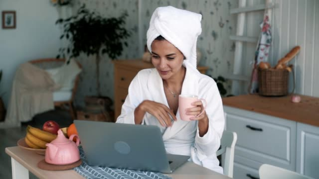vidéos et rushes de fille avec la serviette sur la tête ayant le chat vidéo sur l'ordinateur portatif et boit le thé, le mouvement lent - peignoir