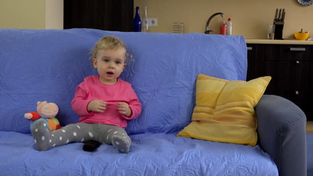 girl with tv remote control watching television and showing true emotions - telecomando background video stock e b–roll