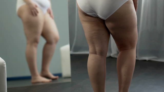 vídeos de stock e filmes b-roll de girl with weight problems looking at her legs in mirror, touching them with hand - corpulento