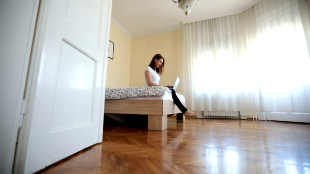 Girl working in bedroom One woman, sitting on the bedroom bed, using laptop computer. double bed stock videos & royalty-free footage