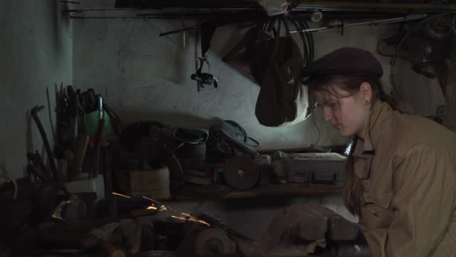 A girl works in an old home workshop