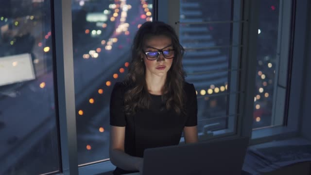 girl works in office in late evening against background of lights of the night of the city. young business woman with a monitor reflection in glasses