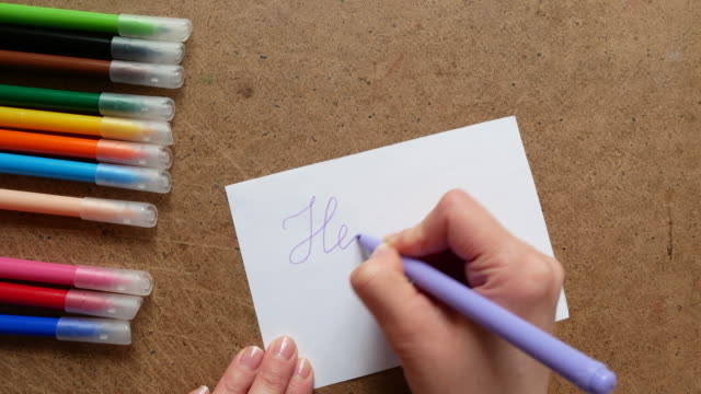 A girl writes hello on paper.