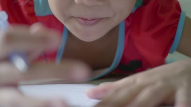 flickan skriver ner i en antecknings bok. - linjerat papper bakgrund bildbanksvideor och videomaterial från bakom kulisserna