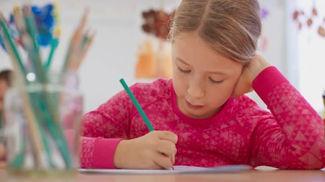 ld girl che scrive nel suo taccuino seduto dietro una scrivania in classe - 8 9 anni video stock e b–roll